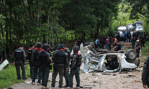 Thai police and army personnel inspect the scene of a bomb attack which left three police officers dead in Thailand's restive southern province of Yala on September 23, 2016. Three police officers were killed on September 23 by a bomb tucked beneath a road in Thailand's far south, police said, as peace talks appear to falter in the insurgency-plagued region. / AFP PHOTO / KATAWUT CHUM
